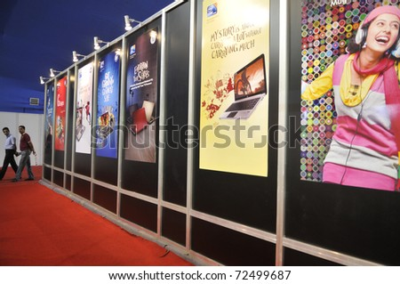 KOLKATA- FEBRUARY 20:  Visitors passing by a panel of displays ,during the Information and Communication Technology (ICT) conference and exhibition in Kolkata, India on February 20, 2011. - stock photo