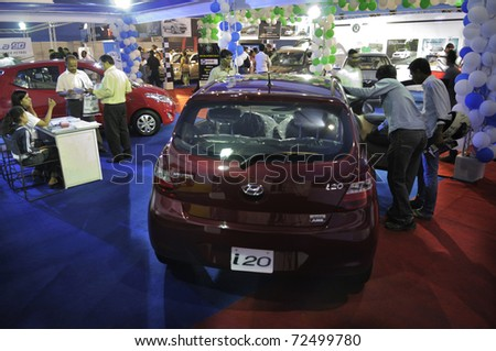 KOLKATA- FEBRUARY 20: Visitors peeping through a brand new Hyundai car, during the Information and Communication Technology (ICT) conference and exhibition in Kolkata, India on February 20, 2011. - stock photo