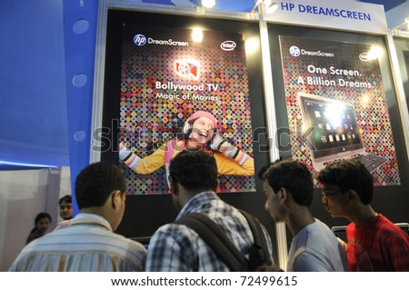 KOLKATA- FEBRUARY 20: Young adults checking a HP DreamScreen , during the Information and Communication Technology (ICT) conference and exhibition in Kolkata, India on February 20, 2011. - stock photo