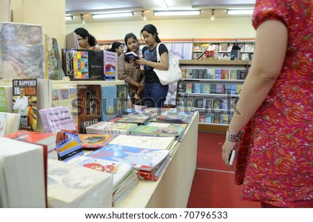 KOLKATA- FEBRUARY 4: Young girls flips through books at a large collection of English book stall during the 2011 Kolkata Book Fair in Kolkata, India on February 4, 2011. - stock photo