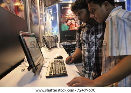 KOLKATA- FEBRUARY 20: Young teens looking at the HP DreamScreen, during the Information and Communication Technology (ICT) conference and exhibition in Kolkata, India on February 20, 2011. - stock photo