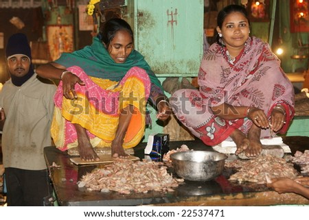 KOLKATA, INDIA - DECEMBER 18: Unknown women in brightly colored sari's shelling prawns in the fish market on December 18, 2008 in Kolkata, West Bengal, India - stock photo
