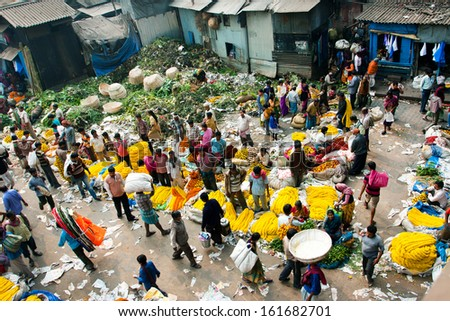 KOLKATA, INDIA - Feb 11: View of Mullik Ghat Flower Market with people scurrying around on February 11, 2013. The market is more than 125 years old. More than 2000 sellers work in the market every day
