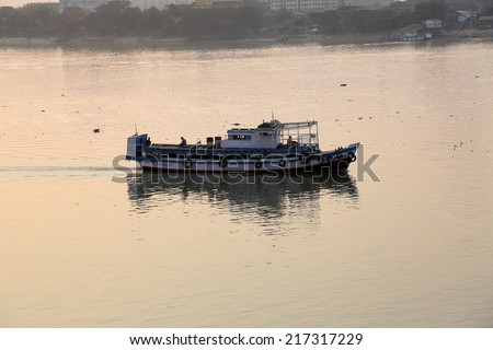 KOLKATA, INDIA - FEBRUARY 08:Old ferry boat crosses the Hooghly River nearby the Howrah Bridge on February 08, 2014. To use the ferry is easy, fast and cheap way how to cross the Hooghly River.