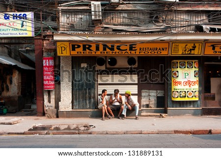 KOLKATA, INDIA - JAN 20: Three asian men talking near the closed restaurant at hot day on January 20, 2013. Third biggest indian city Kolkata with its suburbs is home to approximately 14.1 mill.people