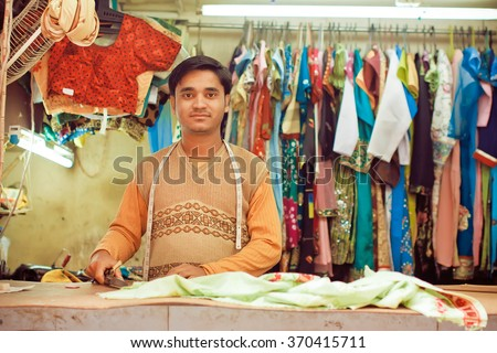 KOLKATA, INDIA - JAN 10: Young tailor sews clothes in a workshop for making dresses on January 10, 2016. Third biggest indian city Kolkata with suburbs is home to approximately 14 mill.people - stock photo