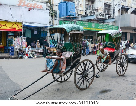 KOLKATA, INDIA - JUL 8, 2015. Rickshaw driver working in Kolkata, India. Rickshaws have been around for more than a century, but they could soon be a thing of the past.