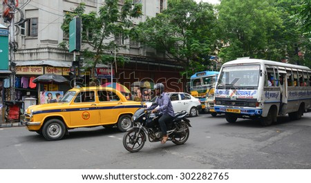 KOLKATA, INDIA - JUL 8, 2015. Vehicles and people on street in Kolkata, India. Kolkata metropolitan area is spread over 1,886.67 km2. - stock photo