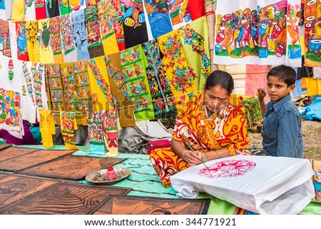 KOLKATA, INDIA - NOVEMBER 28: A craftswoman with her child paints on colorful handicraft items for sale during the annual State Handicrafts Expo 2015 on November 28 2015 in Kolkata West Bengal India. - stock photo