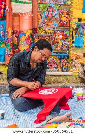 KOLKATA, INDIA - NOVEMBER 28: An Indian artist paints on colorful handicraft items for sale during the annual State Handicrafts Expo 2015 on November 28, 2015 in Kolkata, West Bengal, India. - stock photo
