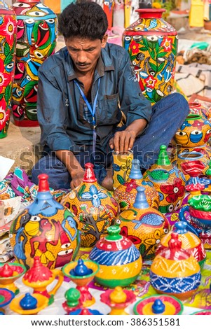 KOLKATA, INDIA - NOVEMBER 24: An Indian craftsman creates colorful handicraft items for sale during the annual State Handicrafts Expo 2015 on November 24, 2015 in Kolkata, West Bengal, India. - stock photo