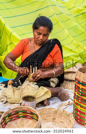 KOLKATA, INDIA - NOVEMBER 28: An Indian craftswoman weaves cane baskets for sale during the annual State Handicrafts Expo 2015 on November 28, 2015 in Kolkata, West Bengal, India. - stock photo