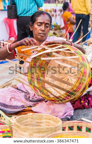 KOLKATA, INDIA - NOVEMBER 24: An Indian craftswoman weaves cane baskets for sale during the annual State Handicrafts Expo 2015 on November 24, 2015 in Kolkata, West Bengal, India. - stock photo
