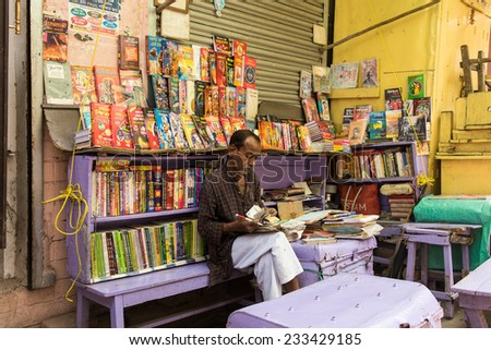 KOLKATA, INDIA - NOVEMBER 22: An unidentified bookseller counts his day's earning on November 22, 2014 at College Street Book Market in Kolkata, West Bengal, India. - stock photo