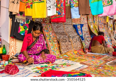 KOLKATA, INDIA - NOVEMBER 28: Indian craftswomen paint on colorful handicraft items for sale during the annual State Handicrafts Expo 2015 on November 28, 2015 in Kolkata, West Bengal, India. - stock photo