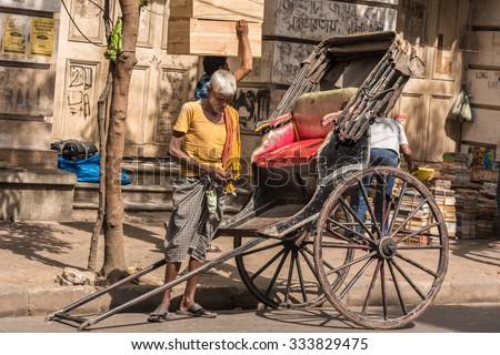 KOLKATA, INDIA - OCTOBER 31: An Indian Rickshaw puller counts his earnings on October 31, 2015 at College Street in Kolkata, West Bengal, India. - stock photo