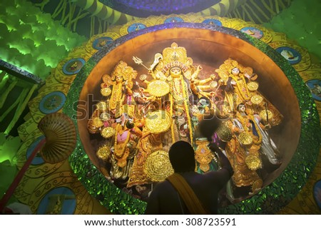 KOLKATA , INDIA - OCTOBER 2, 2014 : Priest praying to Goddess Durga, Durga Puja festival ritual. It is the biggest religious festival of Hinduism and Bengali Community. Documentary editorial. - stock photo