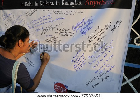 KOLKATA - MARCH 16 :A woman writing solidarity messages on a message board  during a candle light vigil to protest gang rape of an elderly nun on March 16, 2015 at Allen Park in Kolkata, India. - stock photo