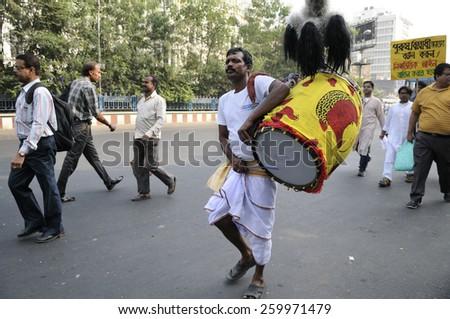 "KOLKATA - NOVEMBER 15 :A ""Dhaki"" accompanying  a rally to celebrate the International Men's Day on November 15, 2014 in Kolkata, India. - stock photo"