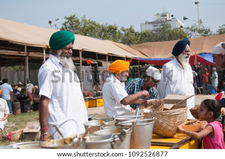 KOLKATA- NOVEMBER 6:Older men volunteers helping to distribute food  during a Langar or community kitchen service which in Sikhism refers to free meal for all  on 6th November, 2014 in Kolkata, India
