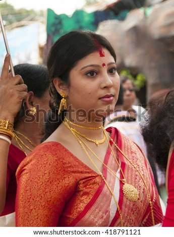 KOLKATA - OCT 17: An unidentified  beautiful woman devotee celebrates Durga puja with red color sindhoor applied on her face during Durga Puja festival on October 17, 2010 in Kolkata, India. - stock photo