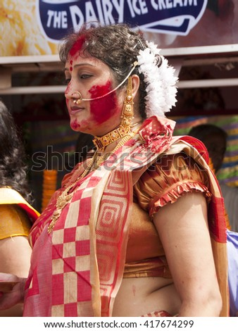 KOLKATA - OCT 17: An unidentified woman devotee celebrates Durga puja with red color sindhoor applied on her face during Durga Puja festival on October 17, 2010 in Kolkata, India. - stock photo