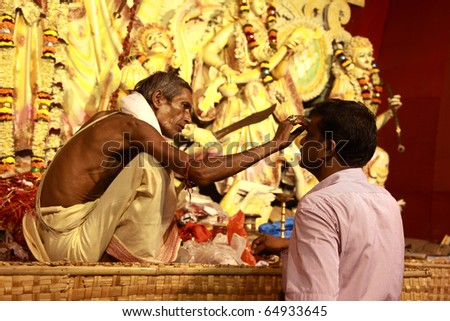 KOLKATA - OCTOBER 15: A hindu priest gives prasada to a devotee  during Durga Puja on October 15, 2010 in Kolkata, India. - stock photo
