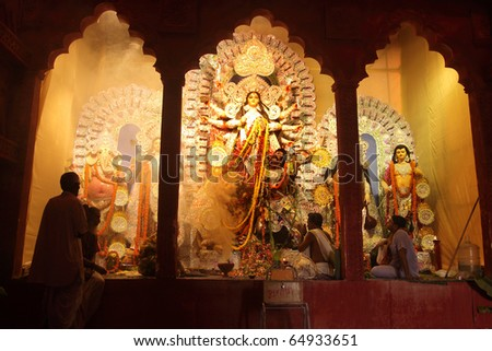 KOLKATA - OCTOBER 16: A hindu priest offers puja rituals in front of huge idols goddess Durga on the day of Durga Puja on October 16, 2010 in Kolkata, India. - stock photo