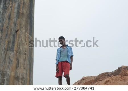 KOLKATA - OCTOBER 26 : A teenage boy standing in front of a chimney before the production season begins inside a brick factory on October 26, 2014 in Kolkata , India. - stock photo