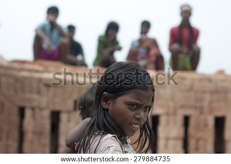 KOLKATA - OCTOBER 26 : Elder sister carrying her brother on her shoulder while other residents sit on top of stacks of bricks  on October 26, 2014 in Kolkata , India.  - stock photo
