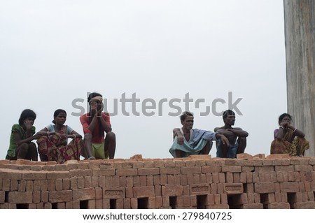 KOLKATA - OCTOBER 26 : Group of brick factory workers sitting on stacks of bricks -brick manufacturing industry in India is a 3 billion dollar industry on October 26, 2014 in Kolkata , India. - stock photo