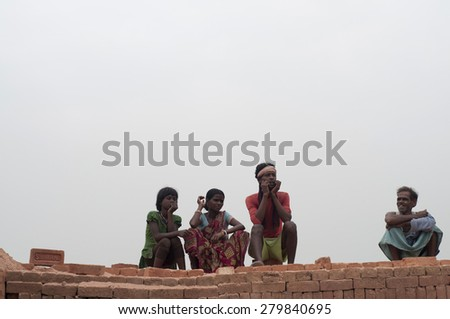 KOLKATA - OCTOBER 26 : Group of brick factory workers sitting on stacks of bricks inside a brick factory where they stay and work under unhealthy conditions on October 26, 2014 in Kolkata , India. - stock photo