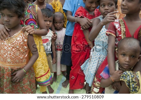 KOLKATA - OCTOBER 26 : Kids lined up inside a brick factory where their family work  and stay under tough and unhealthy conditions on October 26, 2014 in Kolkata , India.  - stock photo