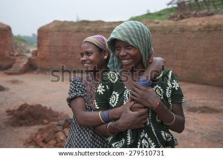 KOLKATA - OCTOBER 26 : Two teenage girls cuddling each other  inside a brick factory where they and their family work under tough and unhealthy conditions on October 26, 2014 in Kolkata , India.  - stock photo
