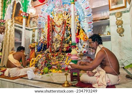 KOLKATA - OCTOBER 2: Unidentified hindu priests worship goddess Durga during the festival of Dussera on October 2, 2014 at Jorasanko, Kolkata, India. It is one of the oldest Durga Puja in Kolkata. - stock photo