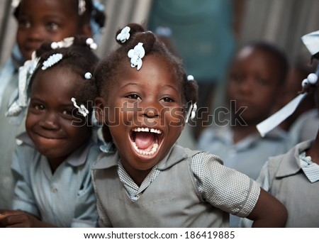 KOLMINY, HAITI - FEBRUARY 12, 2014 - Adorable Haitian school girl in her classroom laughing.   - stock photo