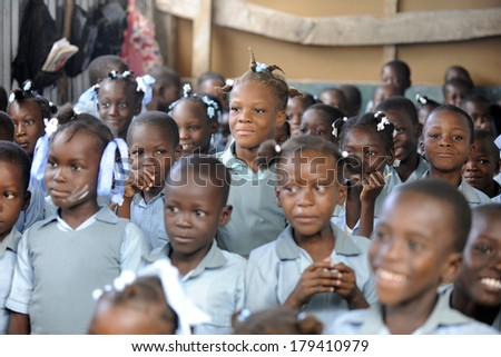 KOLMINY, HAITI - FEBRUARY 12, 2014: Editorial image of unidentified children in a crowded classroom in Kolminy, Haiti on February 12, 2014.  Shallow depth of field with focus on center girl. - stock photo