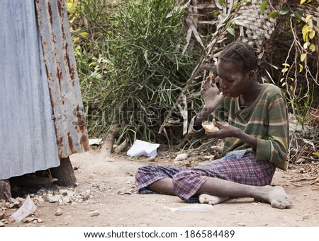 KOLMINY, HAITI - FEBRUARY 12, 2014  Young Haitian girl sitting in the dirt eating peanut butter bread given to her by missionaries. - stock photo
