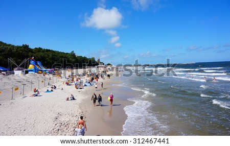 KOLOBRZEG, POLAND - JULY 23, 2015: Many people on a beach with green forest