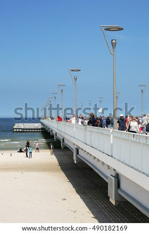 KOLOBRZEG, POLAND - JUNE 19, 2016: Contemporary version of the pier over the Baltic Sea waters and it is after general overhaul that was done in 2014. Many vacationers can be seen on the pier.