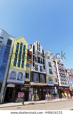 KOLOBRZEG, POLAND - JUNE 23, 2016: Narrow and tall buildings of colorful apartment houses whose facades have been recently renovated together with shops on the ground floor are a tourist attraction - stock photo