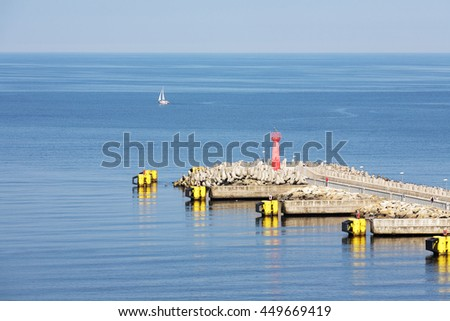 KOLOBRZEG, POLAND - JUNE 22, 2016: The eastern breakwater of the seaport equipped with red signal navigation lantern, it is part of a reconstructed in 2012 port infrastructure - stock photo