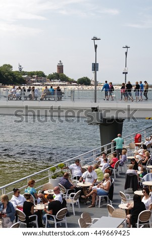 KOLOBRZEG, POLAND - JUNE 19, 2016: Unidentified tourists enjoy the restaurant placed at the end of the concrete pier, other people are resting or are walking along the jetty - stock photo