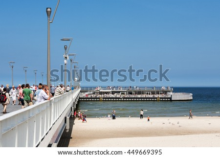 KOLOBRZEG, POLAND - JUNE 19, 2016: Unidentified tourists strolling along the pier and watch the views, the restaurant is located at the end of the jetty where a lot of people enjoy the summer - stock photo