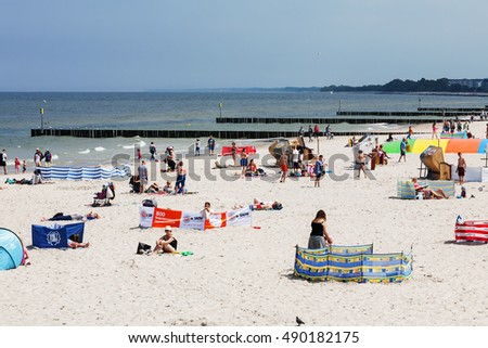 KOLOBRZEG, POLAND - JUNE 19, 2016: Unidentified vacationers are relaxing and sunbathing on the shore of the Baltic Sea