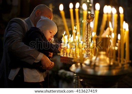 Kolomyia, UKRAINE - May, 2016: Orthodox Easter in Ukraine. An Orthodox priest blesses believers and baskets with painted eggs and kulichi, traditional Easter cake, as they celebrate Orthodox Easter. - stock photo