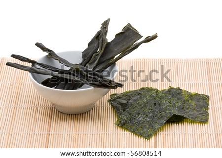 Kombu and kim nori on bamboo mat over white background - stock photo