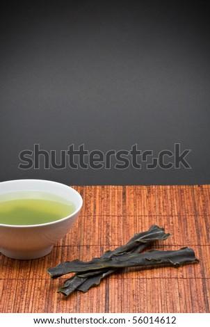 Kombu broth and dried kombu on bamboo mat - stock photo