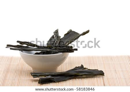 Kombu sea vegetable in bowl on bamboo mat over white background - stock photo