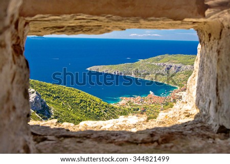 Komiza bay aerial view through stone window from Island of Vis hill, Dalmatia, Croatia - stock photo
